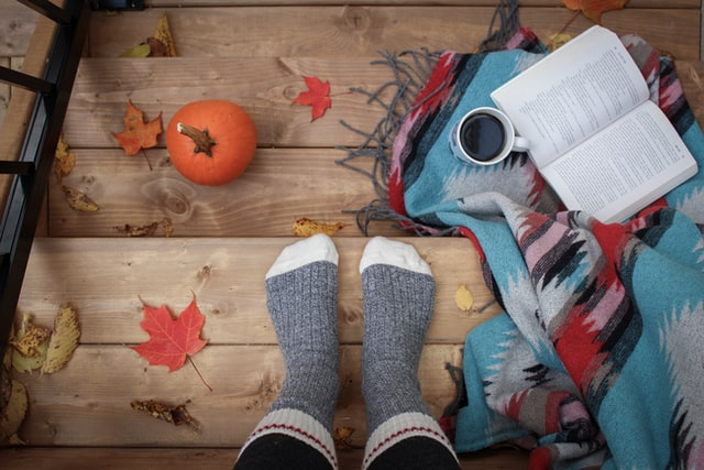 Overhead perspective photo of fall scene on outside porch of pair of feet in socks, wool pattern blanket, cup of coffee, open book, pumpkin and a few colorful leaves